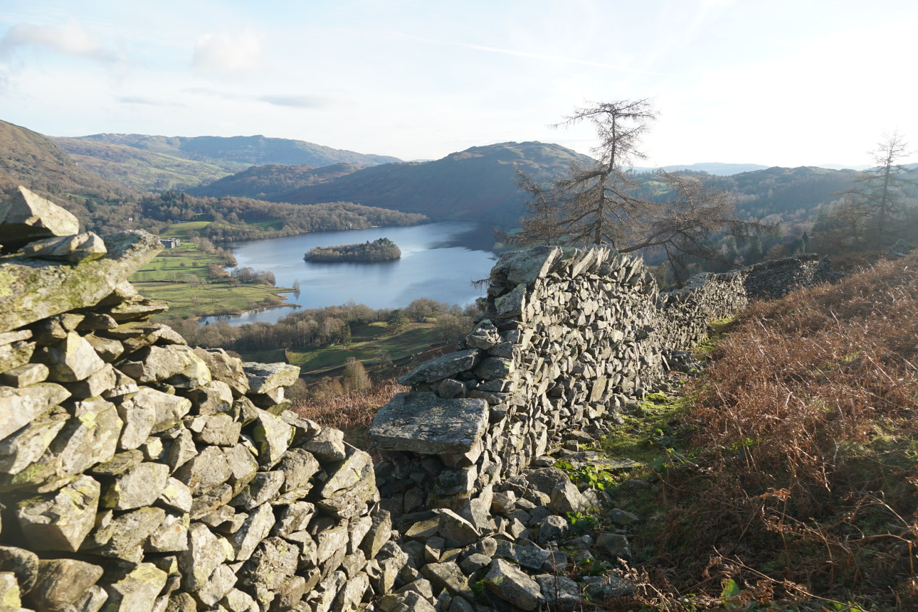 View through a wall gap to Grasmere lake and island. Easy to repair it's not done a bad job – it's been standing intact, through all weathers and seasons, for at least a few hundred years. Taken on 7/12/20 at 12:40 pm.
