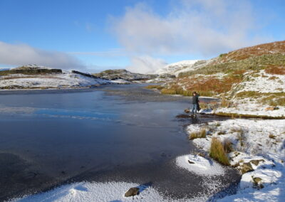 Deborah at the stream inlet with a trail of broken ice leading into the tarn. Taken at 2:08.