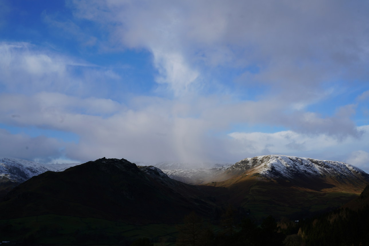 It's snowing in Greenburn between dark Helm Crag and sunlit Steel fell. Taken at 1:40pm.